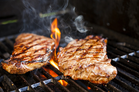 sear: Beef steaks cooking in open flame on barbecue grill