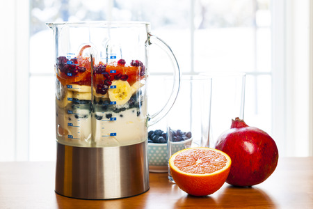 Healthy smoothie ingredients in blender with fresh fruit ready to blend on kitchen table photo