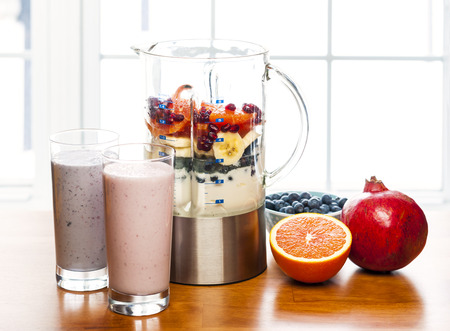blending: Prepared smoothies and healthy smoothie ingredients in blender with fresh fruit ready to blend on kitchen table