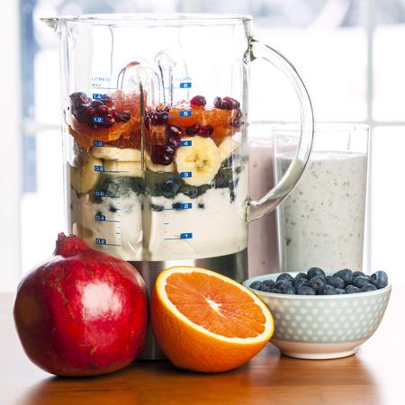 licuadora: Smoothies preparados e ingredientes de batidos saludables en la licuadora con fruta fresca listos para mezclarse en la mesa de la cocina