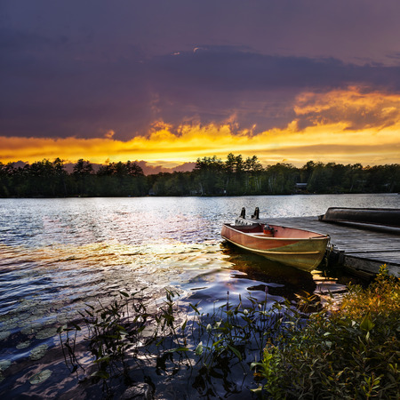 Rowboat tied to dock on beautiful lake with dramatic sunset photo