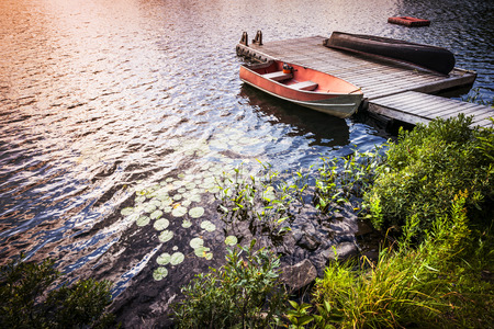 Sunset reflecting in lake water with rowboat tied to wooden dock at rocky shore. Ontario, Canada. photo