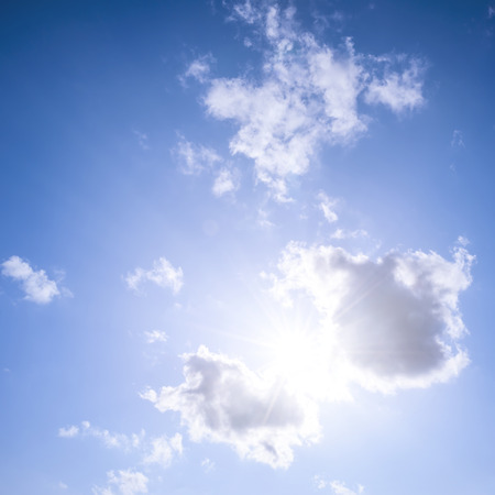 shining through: Square blue sky background with bright sun flare shining through clouds