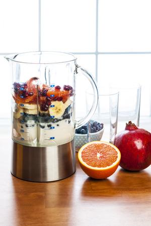 licuadora: Ingredientes de batidos saludables en la licuadora con fruta fresca listos para mezclarse en la mesa de la cocina Foto de archivo