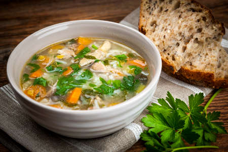 Hähnchen-Reis-Suppe mit Gemüse in eine Schüssel geben und Brot auf rustikalen Tisch