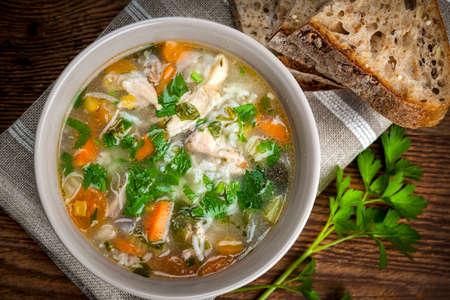 sopa de pollo: Sopa de arroz de pollo con verduras en un tazón y el pan de arriba