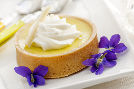 flan: Fresh gourmet lemon dessert tart with edible violet flowers garnish Stock Photo