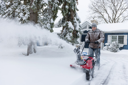 Man using snowblower to clear deep snow on driveway near residential house after heavy snowfall. Stock Photo - 25672664