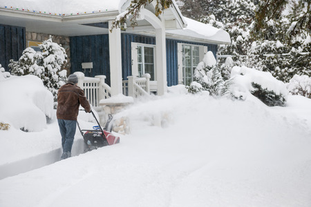 heavy snow: Man using snowblower to clear deep snow on driveway near residential house after heavy snowfall