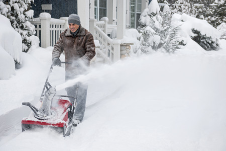 Mann mit Schneefräse zu viel Schnee auf Auffahrt in der Nähe von Wohnhaus nach schweren Schneefällen zu löschen.