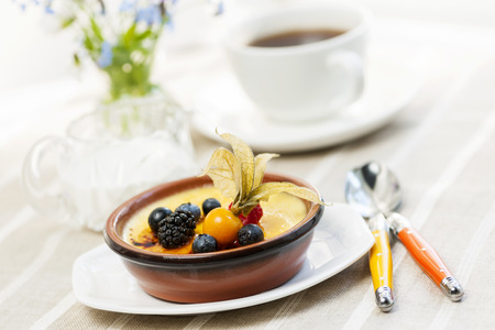 french cafe: Sweet creme brulee dessert topped with fresh berries and coffee