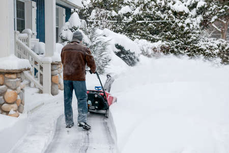 outside machines: Man using snowblower to clear deep snow on driveway near residential house after heavy snowfall