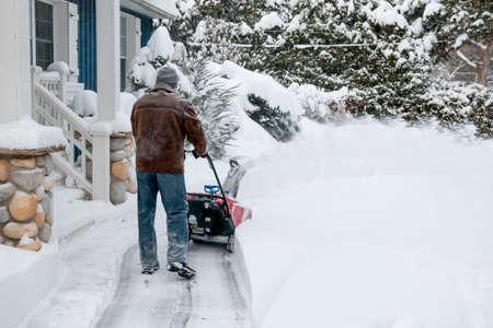 Mann mit Schneefräse zu viel Schnee auf Auffahrt in der Nähe von Wohnhaus nach schweren Schneefällen zu löschen