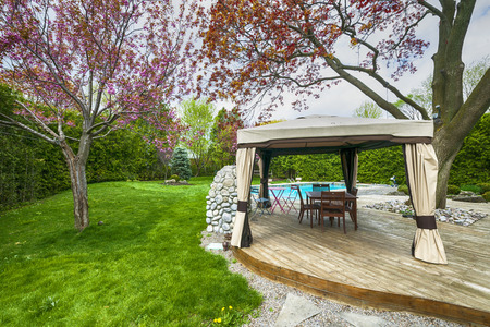 Backyard of residential house in spring with wooden deck and gazebo photo