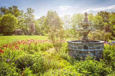 Lush green garden with stone fountain and gazebo in early morning. St. Annes spa, Grafton, Ontario, Canada. photo