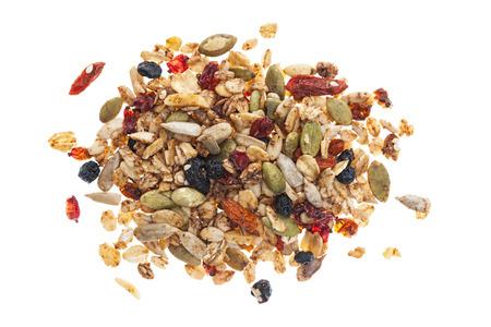 avena en hojuelas: Pila de granola hecha en casa con varias semillas y bayas disparó desde arriba aislado sobre fondo blanco