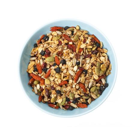 avena en hojuelas: Tazón de granola hecha en casa con varias semillas y bayas disparó desde arriba aislado en el fondo blanco