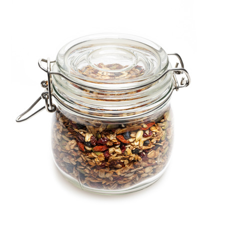 stored: Homemade granola stored in glass jar isolated on white background