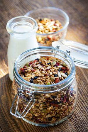 Homemade granola in open glass jar and milk or yogurt  on rustic wooden background photo