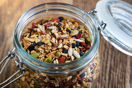 Homemade granola in open glass jar on rustic wooden background photo
