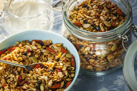 Serving of homemade granola in blue bowl and milk or yogurt on table with linens Stock Photo