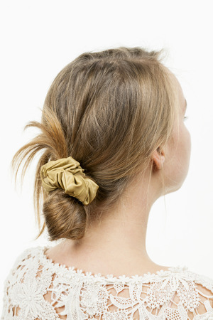 scrunchie: Studio shot of young woman with casual messy chignon hairstyle Stock Photo