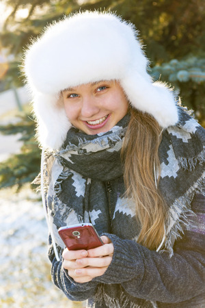 Portrait of teenage girl holding mobile phone outside in winter photo