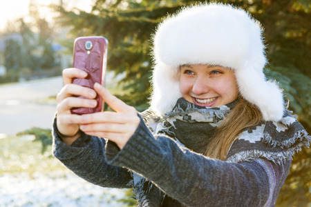 Portrait of teenage girl taking selfie picture with mobile phone outside in winter photo