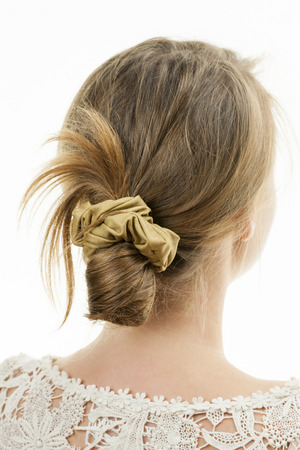 scrunchy: Studio shot of young woman with casual messy chignon hairstyle Stock Photo