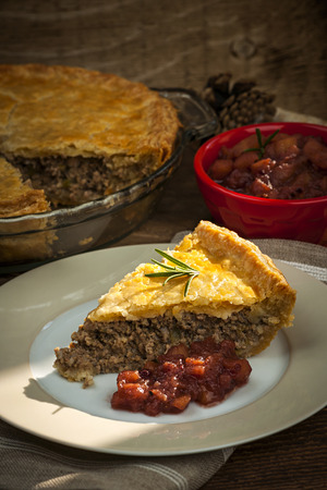 Slice of traditional pork meat pie Tourtiere with apple and cranberry chutney from Quebec, Canada. photo