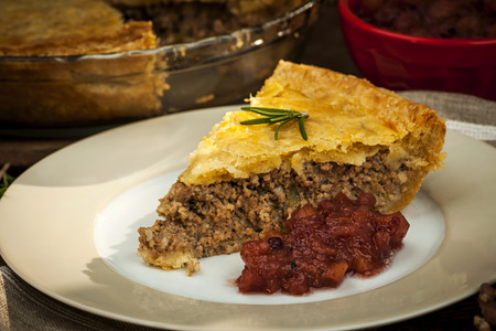meat pie: Slice of traditional pork meat pie Tourtiere with apple and cranberry chutney from Quebec, Canada.