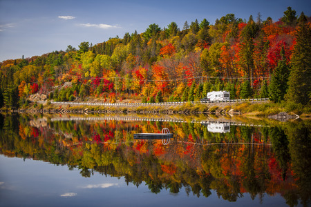 rv: Fall forest with colorful autumn leaves and highway 60 reflecting in Lake of Two Rivers.  Algonquin Park, Ontario, Canada.
