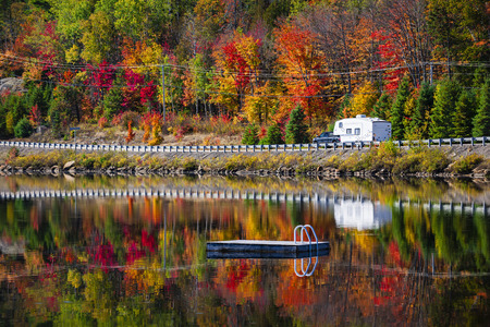 ontario: Camper driving though fall forest with colorful autumn leaves reflecting in lake. Highway 60 at Lake of Two Rivers, Algonquin Park, Ontario, Canada.