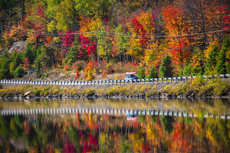provincial forest parks: Scenic route through fall forest with colorful autumn foliage reflecting in lake. Highway 60 at Lake of Two Rivers, Algonquin Park, Ontario, Canada.