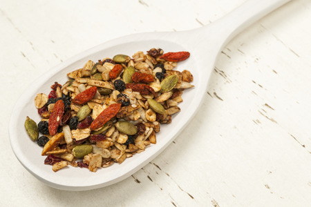 seeds of various: Toasted homemade granola with various seeds and berries in white wooden spoon on wood background