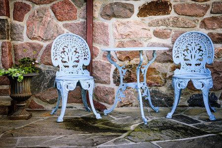 garden furniture: Blue painted metal outdoor furniture on stone patio Stock Photo