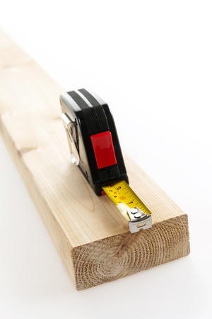 Metal imperial metric tape measure measuring two by four lumber on white background photo