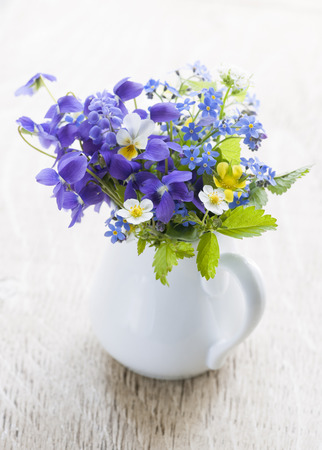 pansies: Bouquet of wild flowers in white vase on wood background, studio shot