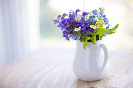 pansies: Bouquet of wild flowers in white vase on rustic wooden table near window with copy space, natural light Stock Photo