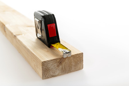 Metal imperial metric tape measure measuring two by four lumber on white background Stock Photo