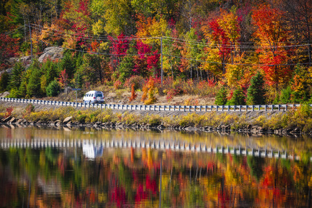 Camper driving though fall forest with colorful autumn leaves reflecting in lake. Highway 60 at Lake of Two Rivers, Algonquin Park, Ontario, Canada. photo