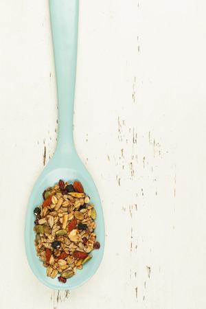 avena en hojuelas: Granola hecha en casa con varias semillas y bayas en una cuchara de madera dispararon desde arriba