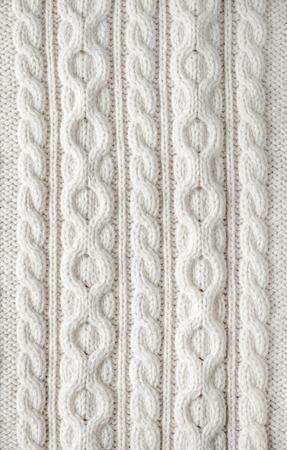Knitbeschaffenheit aus weißer Wolle Gestrick mit einem Kabel-Muster als Hintergrund