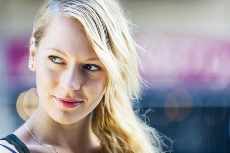 sidelong: Portrait of young blonde woman looking to side with copy space Stock Photo