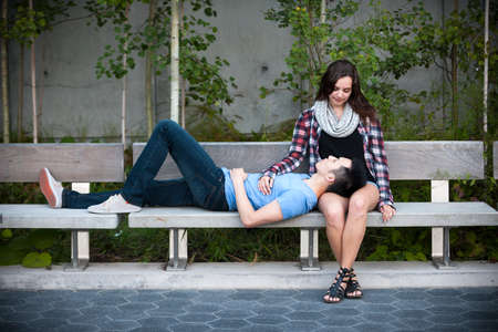 mixed couple: Romantic interracial young couple relaxing on park bench outside Stock Photo
