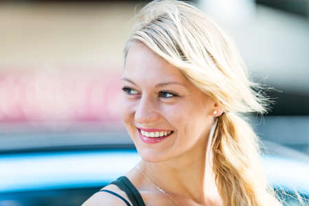 windy city: Candid portrait of young blonde woman smiling with copy space