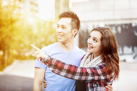 Romantic interracial young couple standing together pointing outside in sunset light with intentional lens flare photo