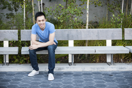 outdoor bench: Young asian man sitting and smiling on park bench with copy space