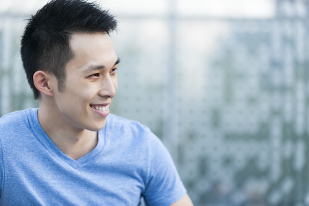 Portrait of confident young asian man in profile smiling on blue background with copy space photo