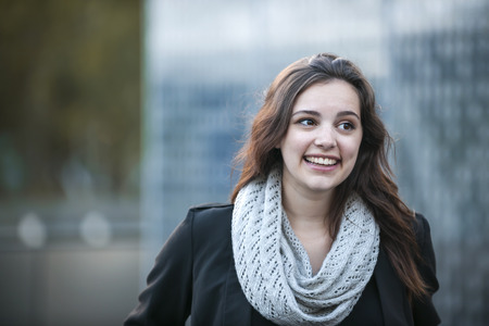 sidelong: Candid portrait of happy young brunette woman smiling with copy space in urban setting